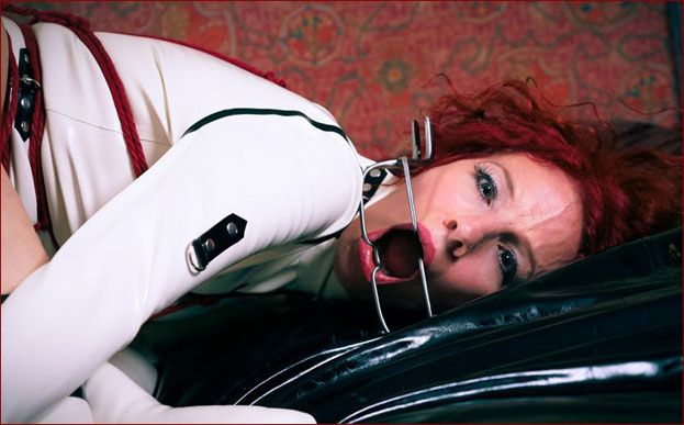 Redheaded lady in rubber straitjacket